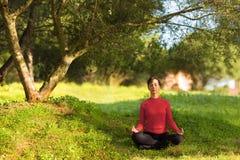 Donna che si siede nell'ambito di un albero e di un meditare Fotografia Stock Libera da Diritti