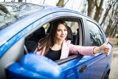 Donna che si siede nell'automobile e che mostra i pollici su sulla strada Immagine Stock