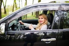 Donna che si siede nell'automobile e che mostra i pollici su sulla strada Immagini Stock