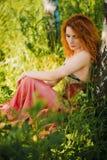 Donna che si siede nell'erba Immagini Stock