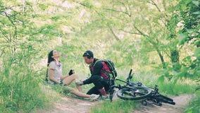 Donna che si siede nell'erba dopo l'incidente della bici video d archivio