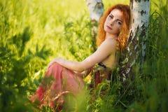 Donna che si siede nell'erba vicino all'albero Fotografie Stock Libere da Diritti