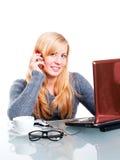 Donna che si siede nell'ufficio e che chiama dal telefono Fotografia Stock