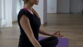 Donna che si siede nella posa del loto di meditazione nella palestra di yoga archivi video