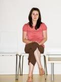 Donna che si siede nella sala di attesa Immagini Stock