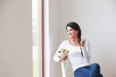 Donna che si siede nella sedia che mangia ciotola di frutta fresca Immagine Stock