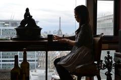 Donna che si siede nella stanza francese di stile a Parigi, fondo la torre Eiffel, Francia immagine stock libera da diritti