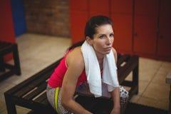 Donna che si siede nello spogliatoio della palestra dopo l'allenamento Fotografie Stock