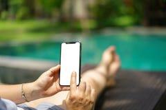 Donna che si siede nello stagno tropicale dello sdraio che tiene lo Smart Phone nero con lo schermo in bianco e la struttura mode immagini stock libere da diritti