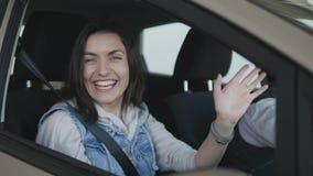 Donna che si siede in nuova automobile comprata, guardando intorno e mano d'ondeggiamento in finestra archivi video