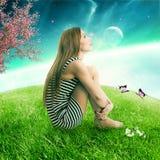 Donna che si siede sopra su un pianeta verde della terra del prato che cerca cielo stellato Immagini Stock