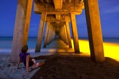 Donna che si siede sotto il pilastro alla notte Fotografie Stock