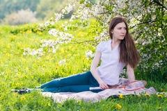 Donna che si siede sotto l'albero del fiore Fotografia Stock