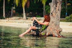 Donna che si siede su contro l'albero sulla spiaggia tropicale Immagine Stock Libera da Diritti
