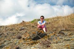 Donna che si siede su Hillside Immagine Stock