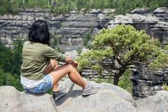 Donna che si siede su un'allerta della roccia Fotografia Stock Libera da Diritti