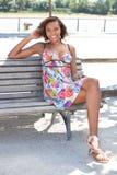Donna che si siede su un banco Fotografie Stock Libere da Diritti