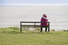 Donna che si siede su un banco Fotografia Stock