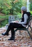 Donna che si siede su un banco con il suo computer portatile Immagine Stock Libera da Diritti