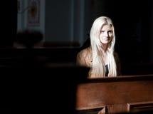 Donna che si siede su un banco di chiesa fotografia stock