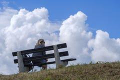 Donna che si siede su un banco e che gode della vista Immagini Stock Libere da Diritti