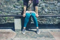 Donna che si siede su un banco fuori immagini stock
