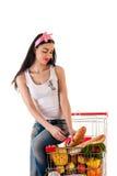 Donna che si siede su un carrello di acquisto Fotografia Stock
