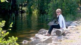 Donna che si siede su un ceppo Immagini Stock