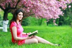 Donna che si siede su un'erba Fotografia Stock