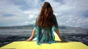 Donna che si siede su un molo in un giorno di rilassamento di estate durante la vacanza stock footage