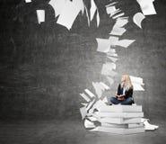 Donna che si siede su un mucchio dei libri che pensano al problema Immagini Stock