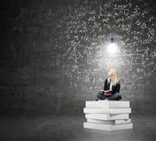 Donna che si siede su un mucchio dei libri che pensano al problema Fotografia Stock Libera da Diritti