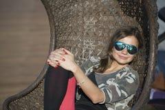 Donna che si siede su un'oscillazione di vimini all'aperto Immagini Stock Libere da Diritti