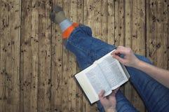 Donna che si siede su un pavimento di legno e che legge un libro Fotografia Stock Libera da Diritti