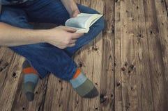 Donna che si siede su un pavimento di legno e che legge un libro Fotografia Stock