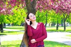 Donna che si siede su un prato inglese verde e che tiene un telefono cellulare Fotografia Stock