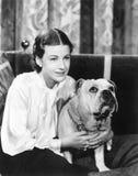 Donna che si siede su un sofà che tiene il suo bulldog (tutte le persone rappresentate non sono vivente più lungo e nessuna propr Immagini Stock