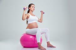Donna che si siede su una palla e su un allenamento di forma fisica con le teste di legno Immagini Stock