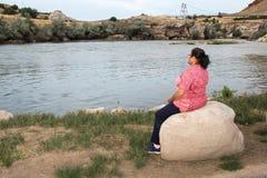 Donna che si siede su una pietra dal fiume Fotografie Stock