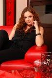 Donna che si siede su una poltrona Immagine Stock
