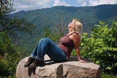 Donna che si siede su una roccia Fotografia Stock Libera da Diritti