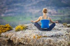 Donna che si siede su una roccia e che gode della vista della valle fotografie stock libere da diritti