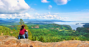 Donna che si siede su una roccia e che gode di bella vista sull'isola di Vancouver, Columbia Britannica, Canada Fotografie Stock
