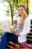 Donna che si siede sul banco con il computer portatile Fotografia Stock Libera da Diritti