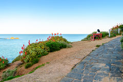 Donna che si siede sul banco con la vista del mare Immagini Stock