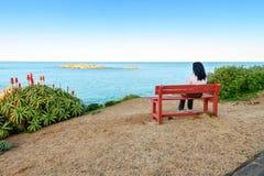 Donna che si siede sul banco con la vista del mare Immagine Stock Libera da Diritti
