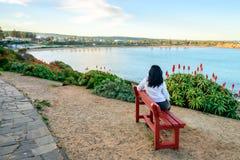 Donna che si siede sul banco con la vista del mare Fotografie Stock