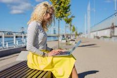 Donna che si siede sul banco esterno e sul lavoro Immagini Stock Libere da Diritti