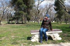 Donna che si siede sul banco in primavera fotografie stock libere da diritti