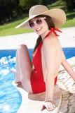 Donna che si siede sul bordo di nuoto nel raggruppamento Fotografie Stock Libere da Diritti